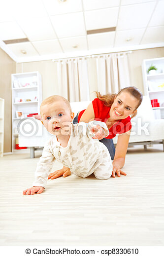 Smiling mommy playing with creeping on floor baby - csp8330610