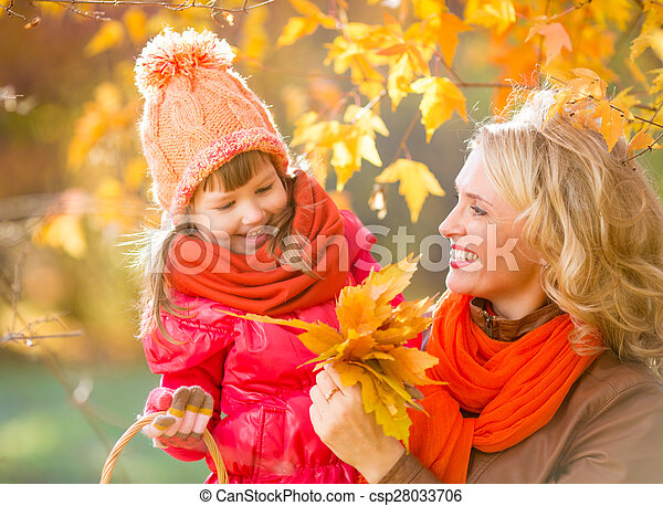 Smiling mother and kid outdoor with autumn yellow leaves - csp28033706
