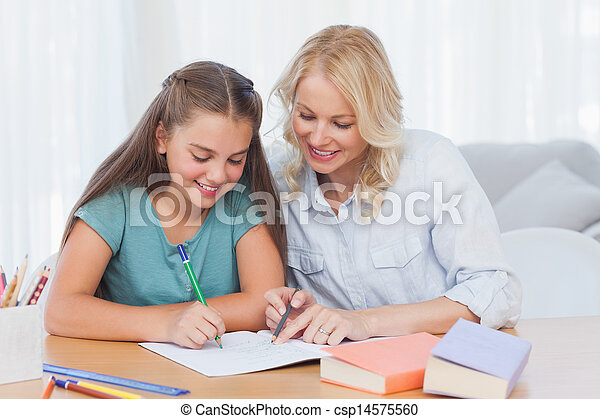 Smiling mother helping daughter with homework - csp14575560