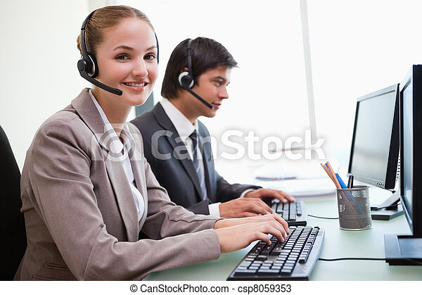 Smiling office workers using computers - csp8059353
