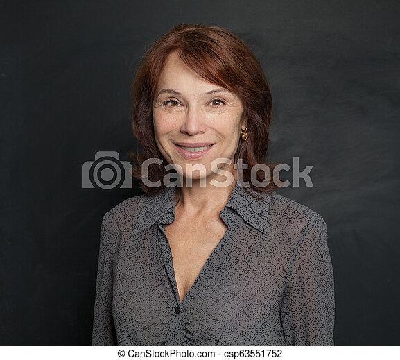 Smiling older woman on black background - csp63551752