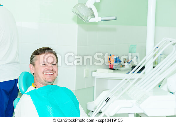 smiling patient looking at camera at the dentist office - csp18419155