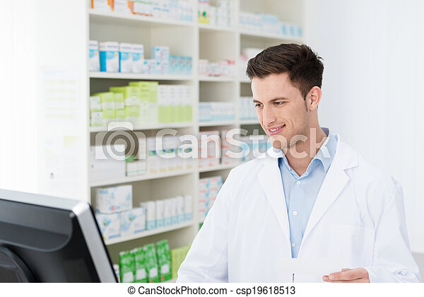 Smiling pharmacist checking stock on his computer - csp19618513