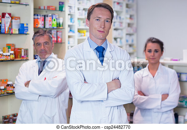 Smiling pharmacy team standing with arms folded - csp24482770