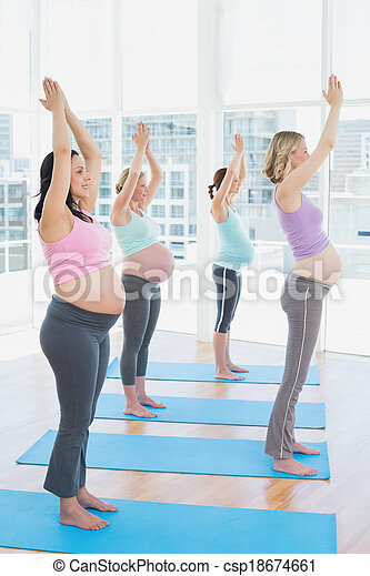 smiling pregnant women in yoga class standing in tree pose