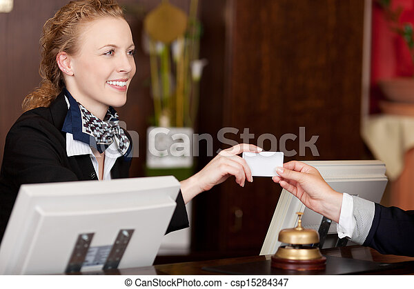 Smiling receptionist handing over a card - csp15284347