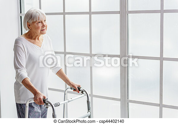 Smiling retiree holding walking aid in her hand. Outgoing female ...