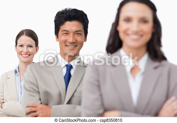 Smiling sales team standing with arms folded - csp8350810