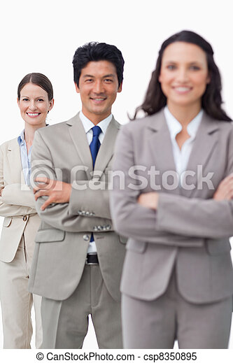 Smiling sales team standing with folded arms - csp8350895