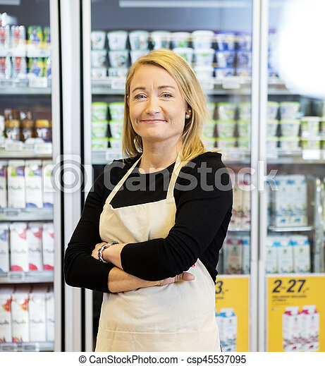 Smiling Saleswoman With Arms Crossed Standing Against Refrigerat - csp45537095