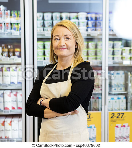 Smiling Saleswoman With Arms Crossed Standing Against Refrigerat - csp40079602