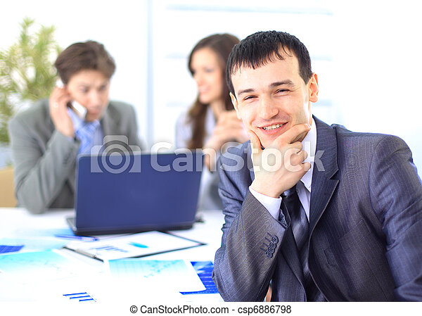 Smiling satisfied businessman looking at camera with his colleagues in the background during a meeting in the office  - csp6886798