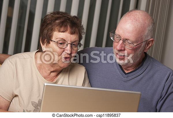 Smiling Senior Adult Couple Having Fun on the Computer - csp11895837