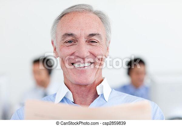 Smiling senior businessman reading  - csp2859839