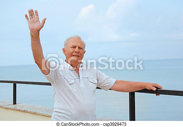 smiling senior on veranda near seacoast, lifted hand upwards - csp3929473