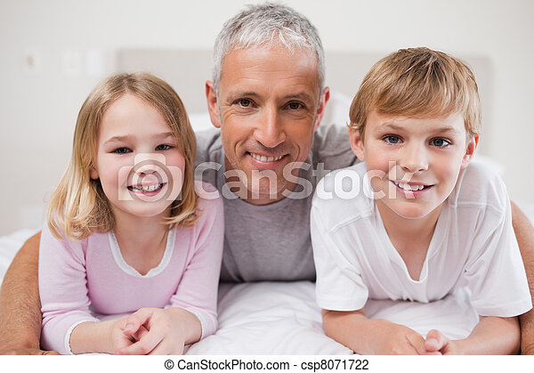 Smiling siblings and their father posing - csp8071722