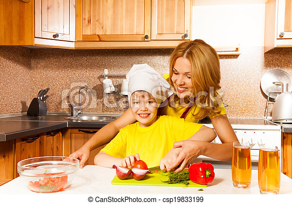Smiling son cuts vegetables on table with mother - csp19833199