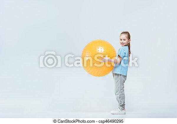 smiling sporty girl holding fitness ball on white - csp46490295