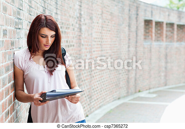 Smiling student reading her notes - csp7365272