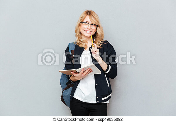 Smiling student with notebook - csp49035892