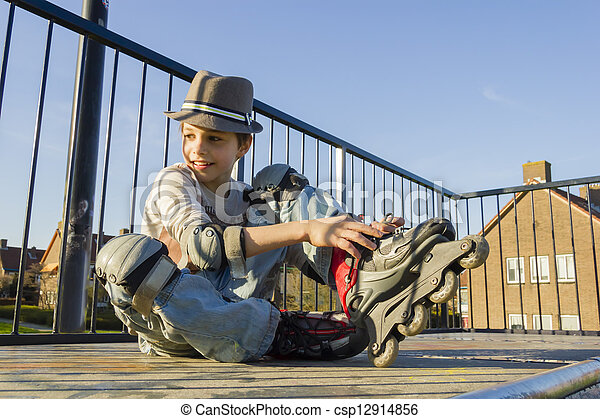 smiling teenage boy in roller-blading protection kit - csp12914856