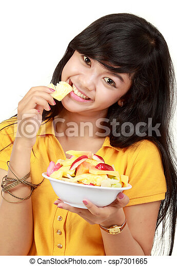 smiling teenager eating a bowl of cut fruits - csp7301665