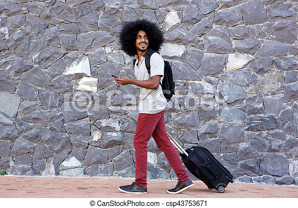 smiling travel man with phone and bags walking outside - csp43753671