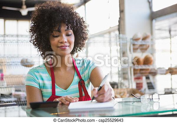 Smiling waitress writing on notepad - csp25529643