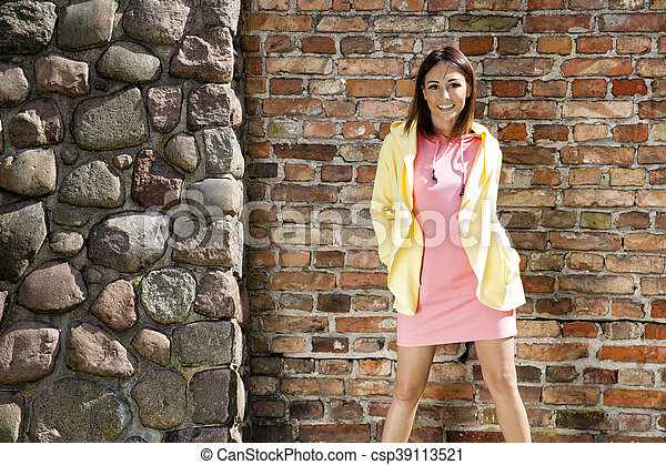 Smiling woman against a brick wall - csp39113521