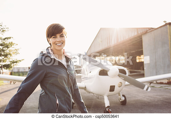 Smiling woman at the airport with light aircraft - csp50053641