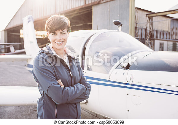 Smiling woman at the airport with light aircraft - csp50053699
