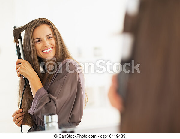 Smiling woman curling hair with straightener - csp16419433