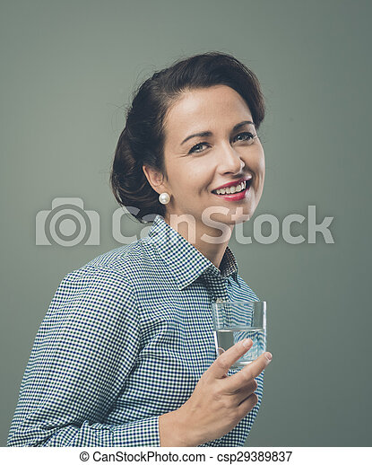 Smiling woman drinking a glass of water - csp29389837
