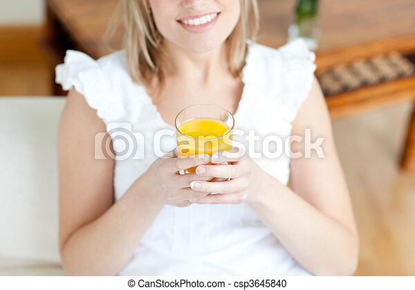 Smiling woman drinking an orange juice - csp3645840