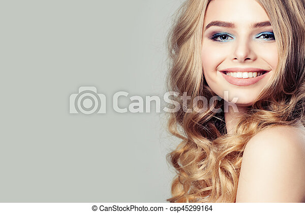 Smiling Woman Fashion Model with Blond Curly Hair on Background - csp45299164