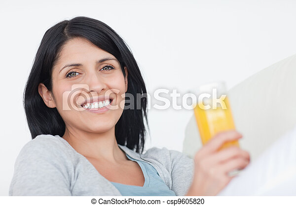 Smiling woman holding a glass of juice - csp9605820