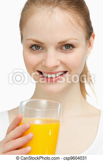 Smiling woman holding a glass of orange juice - csp9604031
