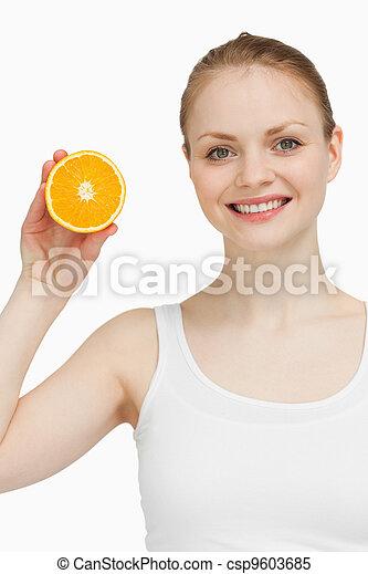 Smiling woman holding an orange - csp9603685