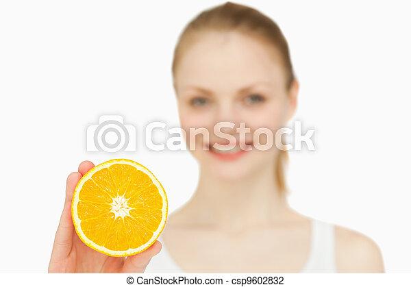 Smiling woman holding an orange - csp9602832