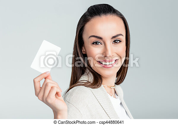 portrait of smiling woman holding credit card in hand and looking to