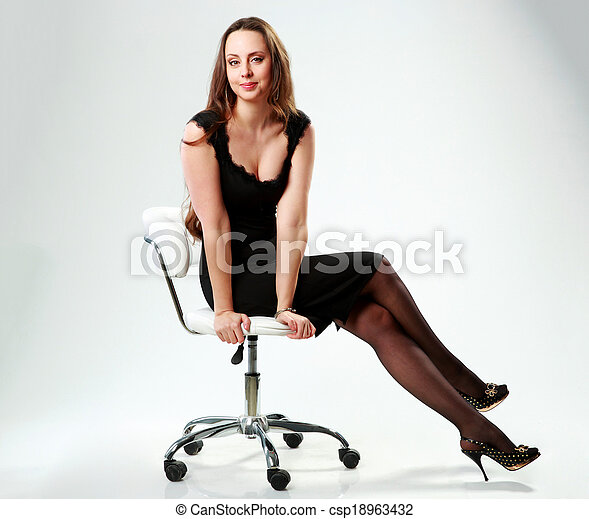 Smiling woman in black dress sitting on the office chair over gray background - csp18963432