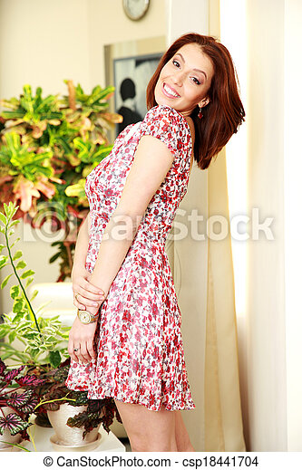 Smiling woman in dress standing at home - csp18441704