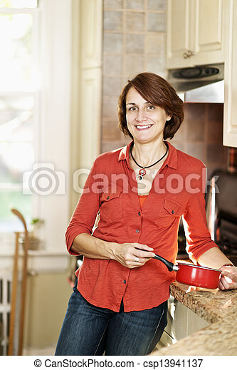 Smiling woman in kitchen at home - csp13941137