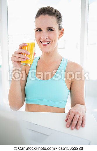 Smiling woman in sportswear holding orange juice - csp15653228