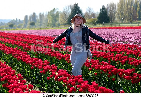 Smiling woman in tulip fields. - csp46863078