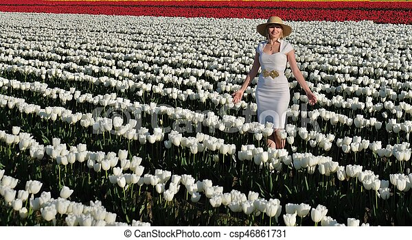 Smiling woman in tulip fields. - csp46861731