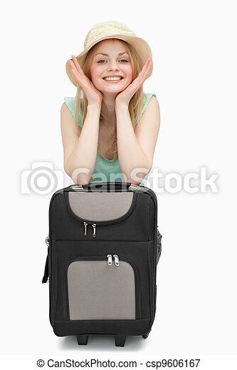 Smiling woman leaning on a suitcase while sitting - csp9606167