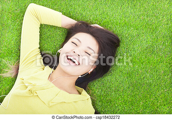 smiling woman listening music and lying on a meadow - csp18432272