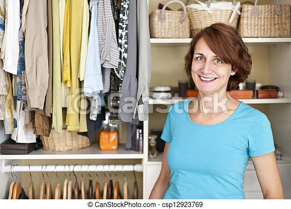 Smiling woman near closet - csp12923769