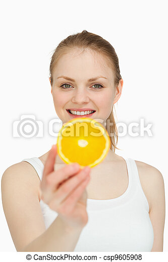 Smiling woman presenting a slice of orange - csp9605908